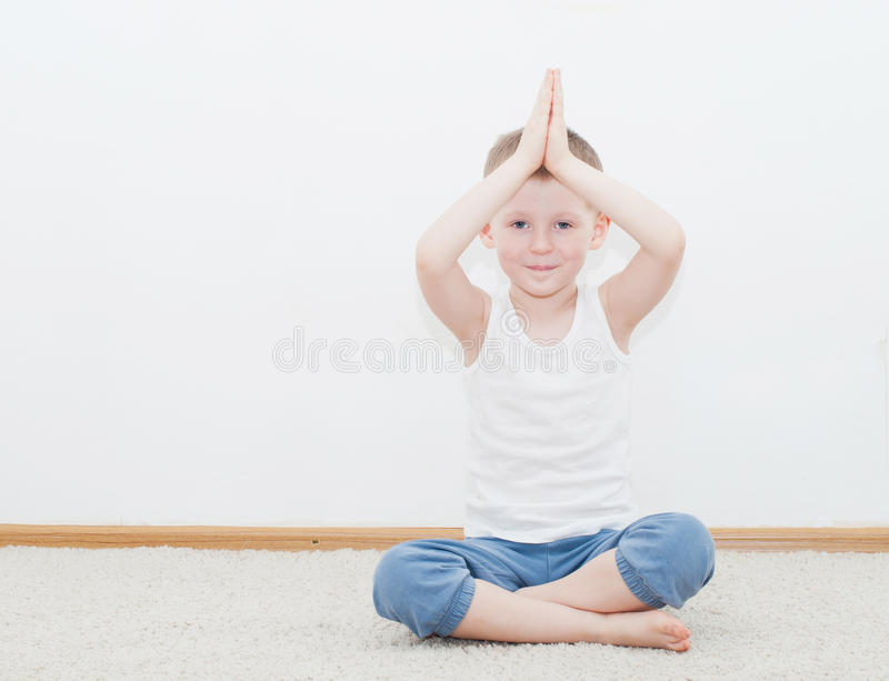 Kid doing yoga relaxing exercise. In his room royalty free stock image