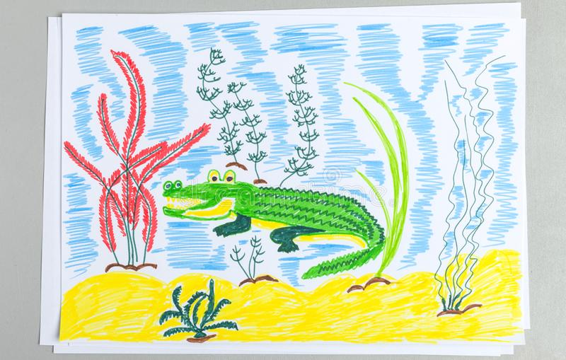 Kid doodle of cute crocodile underwater on sand bottom with seaweeds stock photo