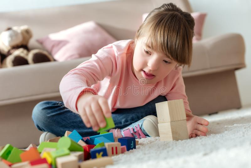 Kid with down syndrome playing. With toy cubes stock photography