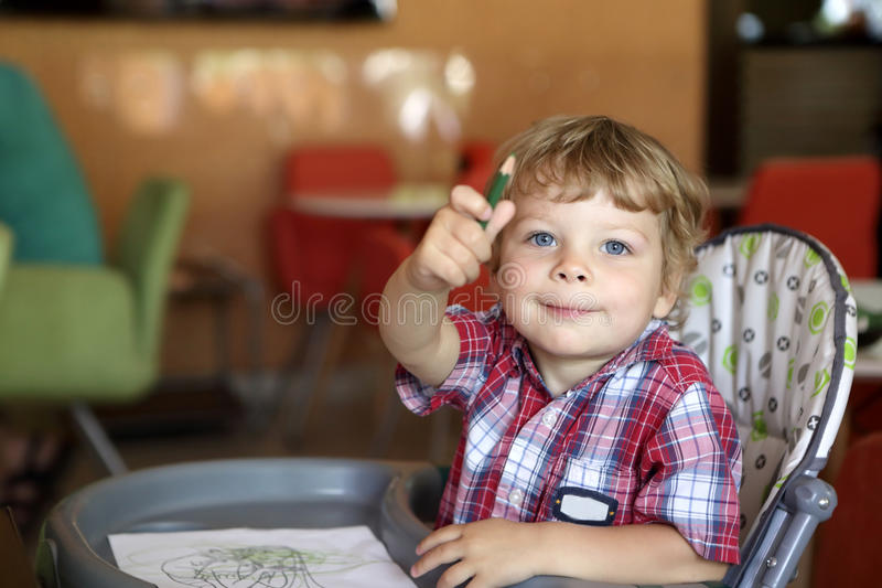 Kid drawing in cafe stock image