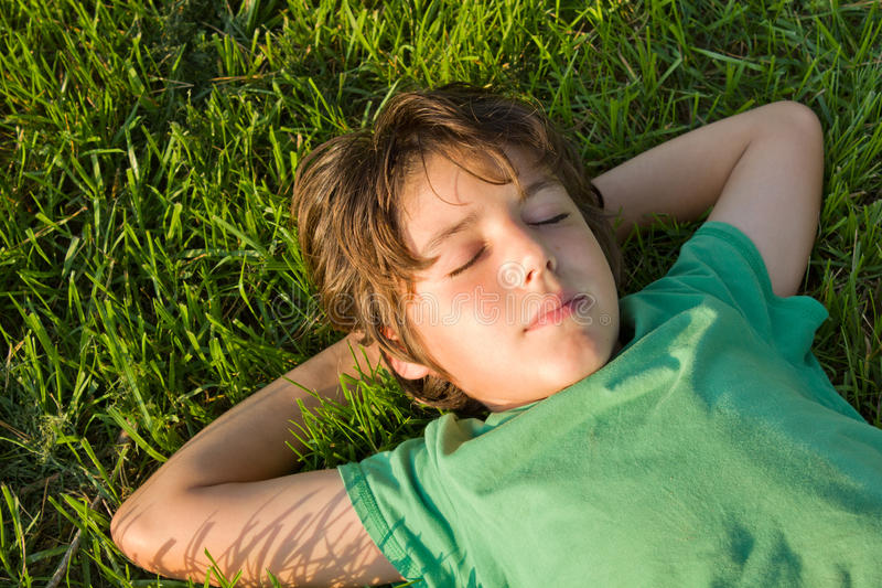 Kid dreaming on grass stock photos