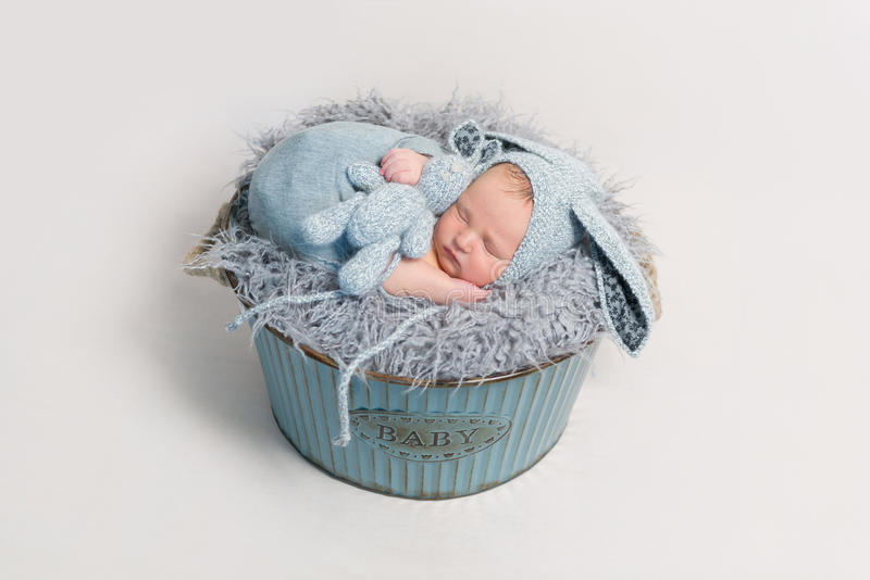Kid dressed as rabbit sleeping with blue toy. Lovely kid dressed as easter rabbit sleeping with his blue rabbit toy in child`s basket stock photography