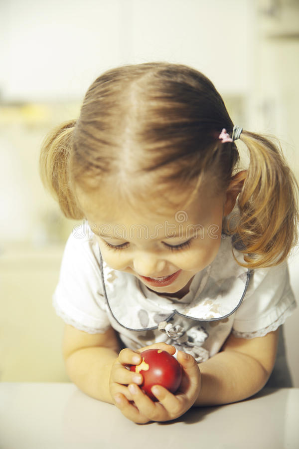 Kid with easter egg. Smiling little girl holding a red easter egg royalty free stock images