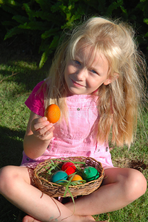 Child with Easter eggs. A beautiful little blond caucasian white girl with proud smiling facial expression showing her colorful Easter eggs which she collected stock photo