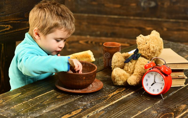 Kid eat food at wooden table. Kid enjoy meal with toy friend. Kid menu. Little kid eating. You are what you eat stock photos
