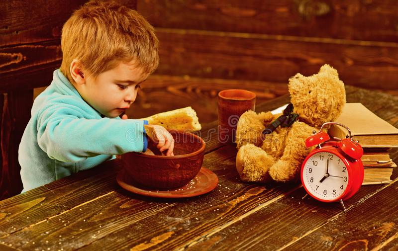 Kid eat food at wooden table. Kid enjoy meal with toy friend. Kid menu. Little kid eating. You are what you eat stock photo