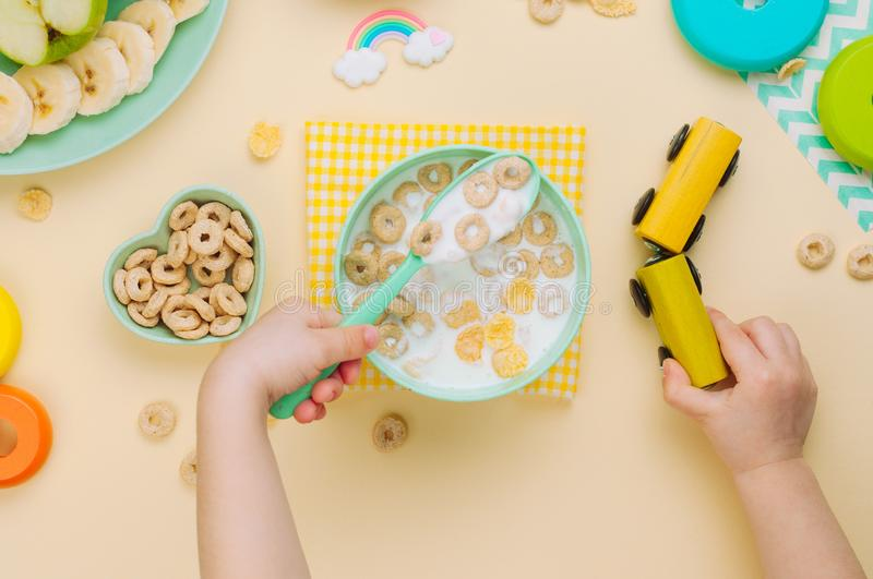Kid eating flakes with milk and playing with wooden train royalty free stock photography