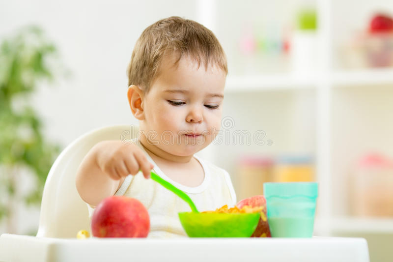 Kid eating healthy food on kitchen stock photography