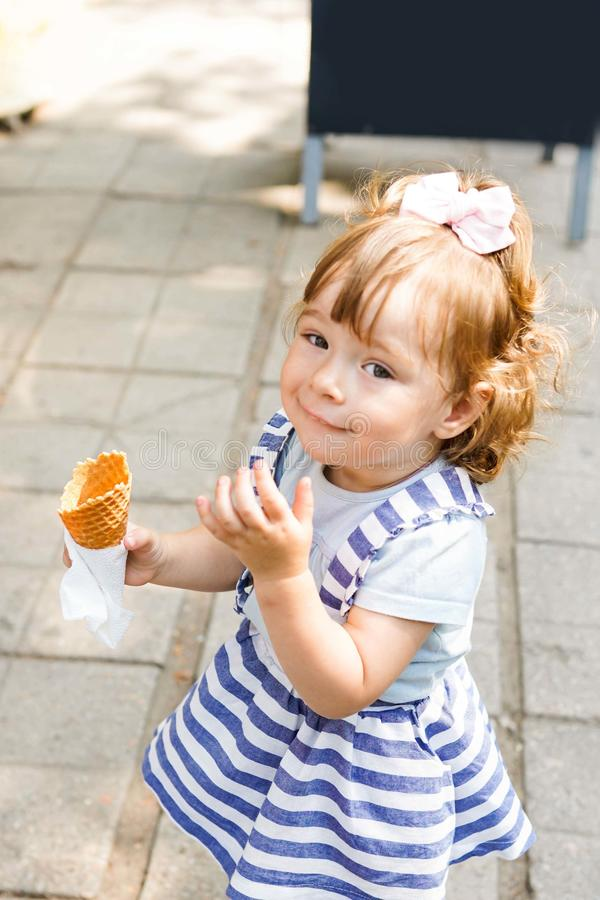 Kid eating ice cream near cafe. Funy curly child with icecream outdoor in the park stock images