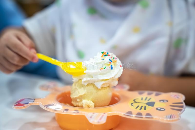 Kid is eating ice-cream and whip cream in the icecream restaurant royalty free stock photo