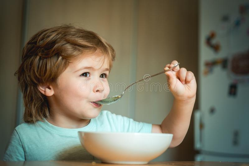 Kid eating. Little boy having breakfast in the kitchen. Parenthood. Happy child. Young kid sitting on the table eating royalty free stock photos