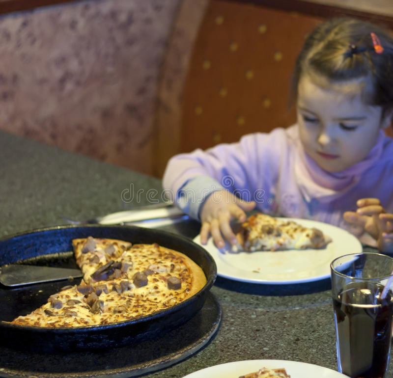 Kid eating pizza in restaurant background royalty free stock photo