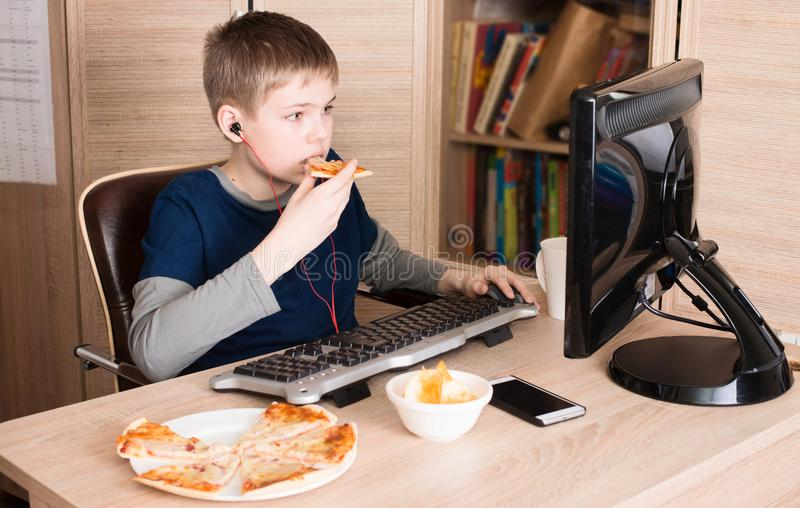 Kid eating pizza and surfing on internet or playing video games. On PS. Boy in headphones eating fast food while using computer in his room stock images