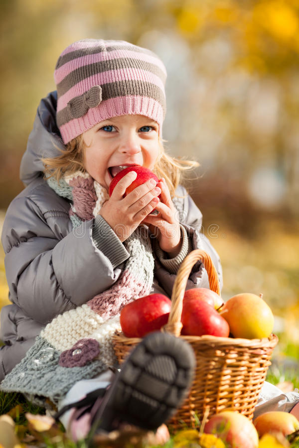 Kid eating red apple. Happy kid eating red apple in autumn park. Healthy lifestyles concept royalty free stock images
