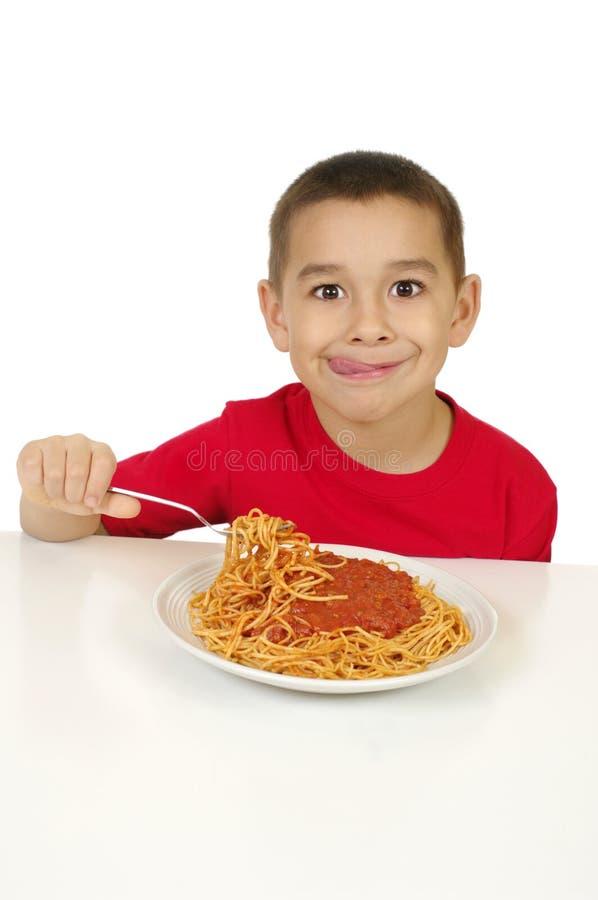 Kid eating spaghetti royalty free stock photography