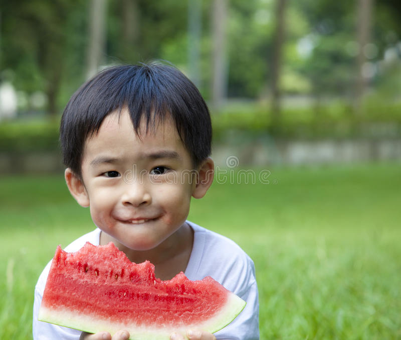 Kid eating watermelon. Cute asian boy eating watermelon on the grass stock images