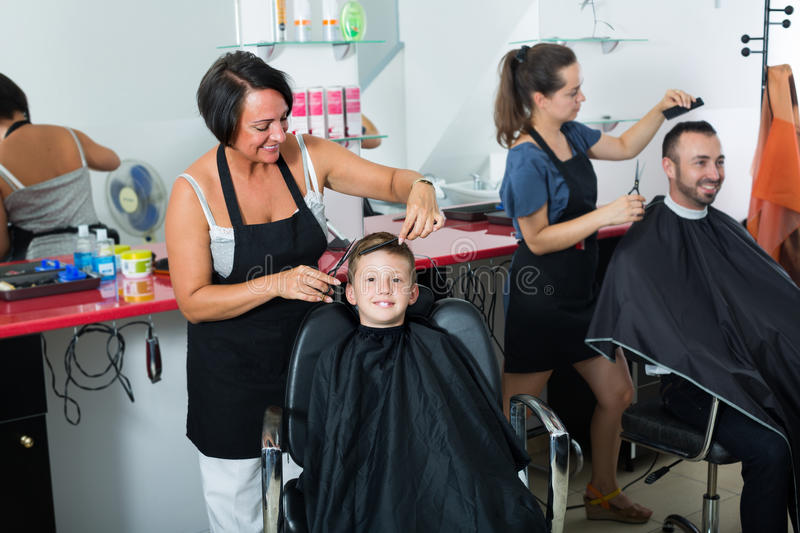 Kid in elementary school age getting hairdo by woman. Smiling kid in elementary school age getting hairdo by women hairdresser in crowded beauty salon stock photography