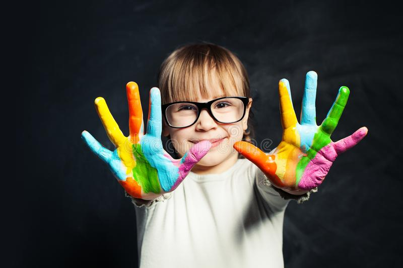 Kid enjoying his painting. Cute child girl with colorful hands on classroom blackboard background. Arts and creative education stock image