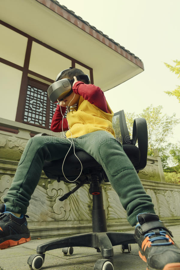 Kid enjoying virtual reality. Chinese kid sitting on chair enjoying virtual reality outdoor