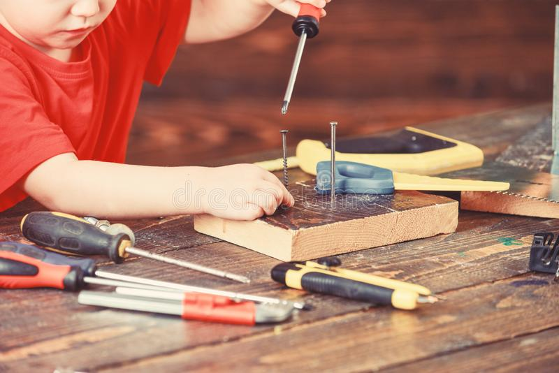 Kid faceless works with screwdriver, wooden background, close up. Child play as builder or repairman with tools in stock photo