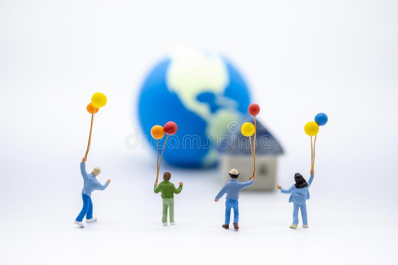 Kid and Family concept. Close up of group children miniature figure playing and holding colorful balloon on white and mini world royalty free stock photo
