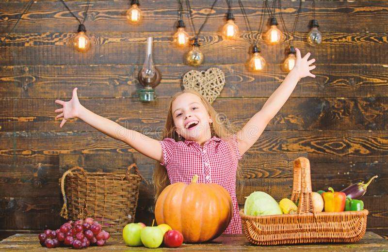 Kid farmer with harvest wooden background. Harvest festival concept. Child little girl enjoy farm life. Organic. Gardening. Grow your own organic food. Girl kid stock image