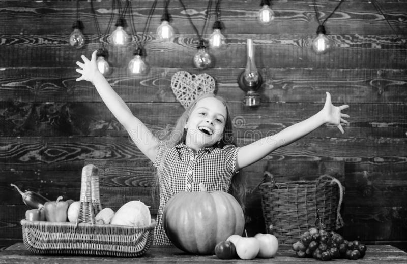 Kid farmer with harvest wooden background. Harvest festival concept. Child little girl enjoy farm life. Organic. Gardening. Grow your own organic food. Girl kid royalty free stock photography