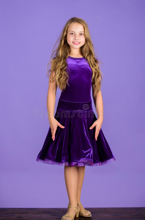 Kid fashionable dress looks adorable. Ballroom dancewear fashion concept. Kid dancer satisfied with concert outfit. Girl. Cute child wear velvet violet dress royalty free stock photo