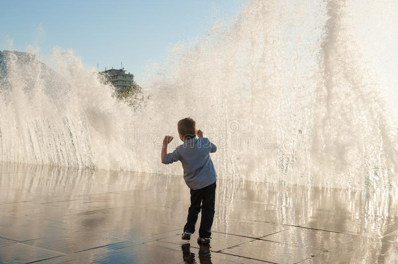Little kid fearfully faces a gigantic wave by the sea in the city stock image