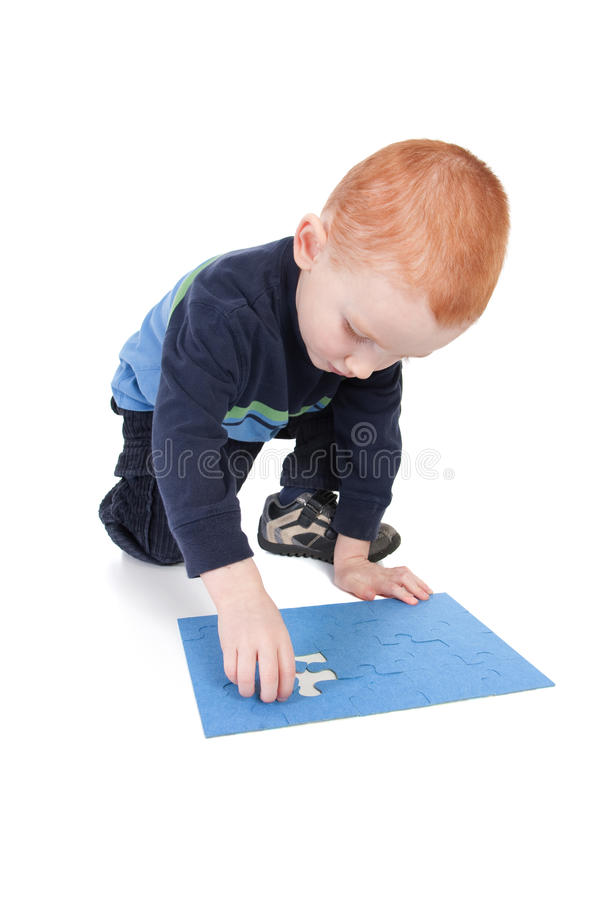 Kid finishing puzzle with last and final piece royalty free stock photos