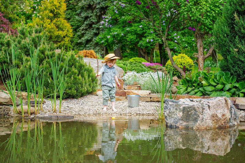 Kid fishing in the pond stock photos