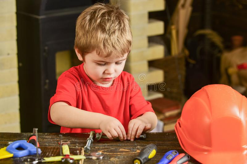 Kid fixing two metal details. Concentrated boy working with bolts. Preschooler helping in workshop stock images