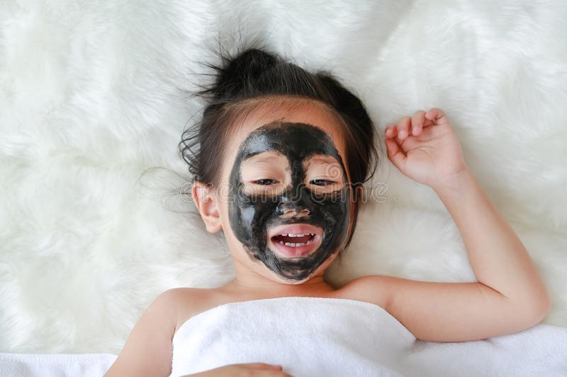 Kid girl in black peeling face mask, beauty concept.  stock photography