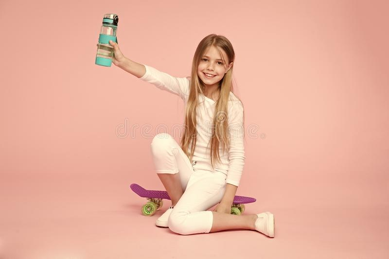 Kid girl care body hydration. Active leisure and water balance. Active and healthy kid drink water. Staying hydrated. Girl happy face holds with water bottle royalty free stock photography