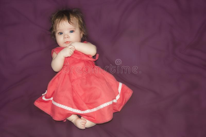 Kid. girl in a carved dress on a purple royalty free stock photos