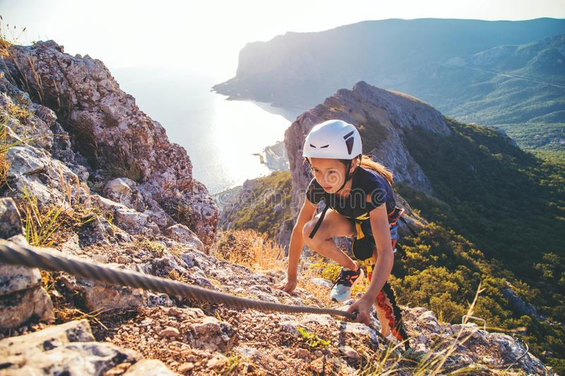 Kid girl climbing mountain. stock images