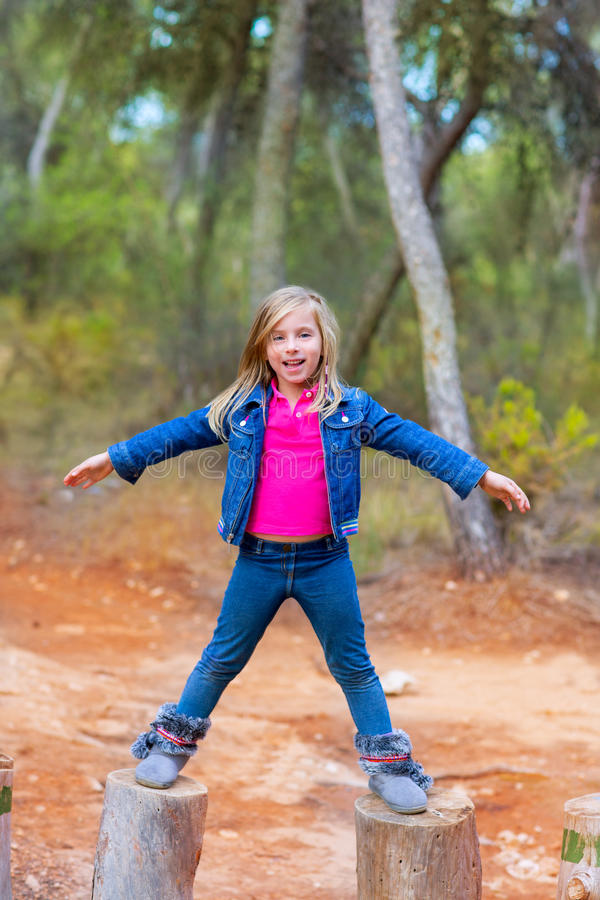 Kid girl climbing tree trunks with open arms royalty free stock image