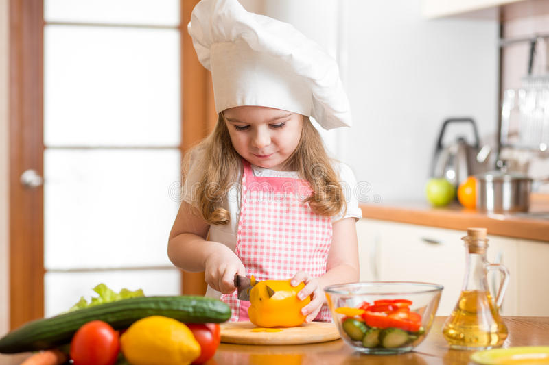 Kid girl cook cutting vegetables royalty free stock image
