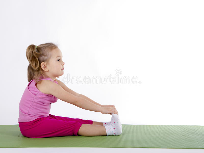 Kid girl doing fitness exercises. Pulls hands to toes stock photo