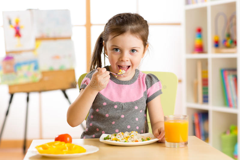 Kid girl eating healthy food at home stock photo