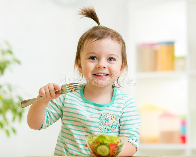 Kid girl eating healthy vegetables food royalty free stock photos