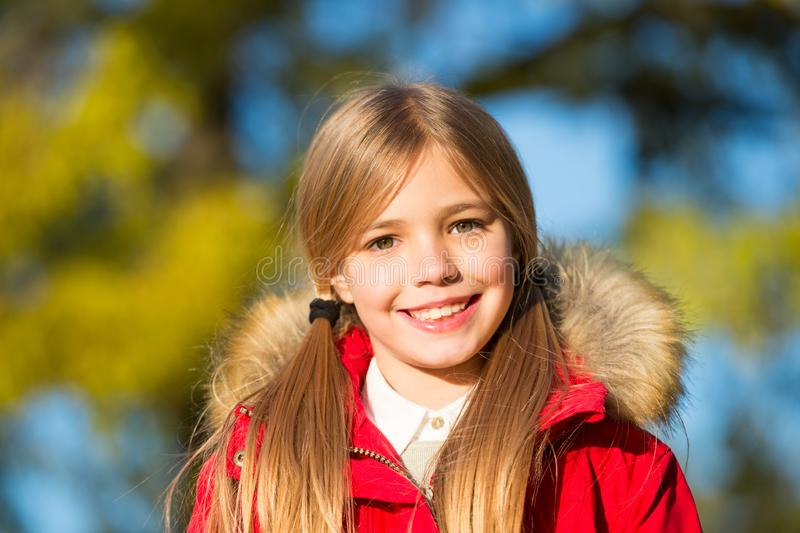 Kid girl enjoy autumn day. Child blonde long hair walking in warm jacket outdoor. Girl charming smile coat enjoy fall royalty free stock photography