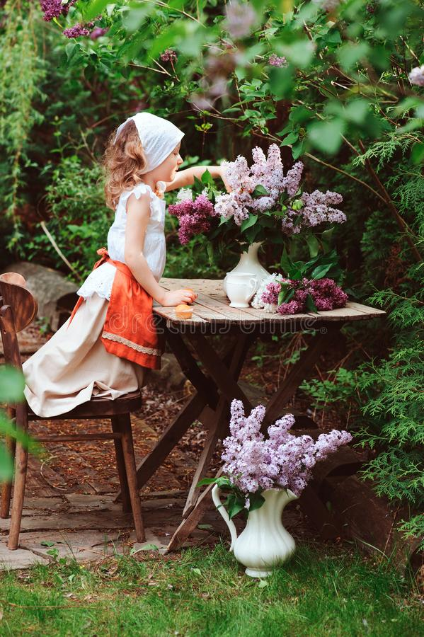 Kid girl at garden tea party in spring day with bouquet of lilacs syringa. Rustic wooden table and vintage dress stock photo
