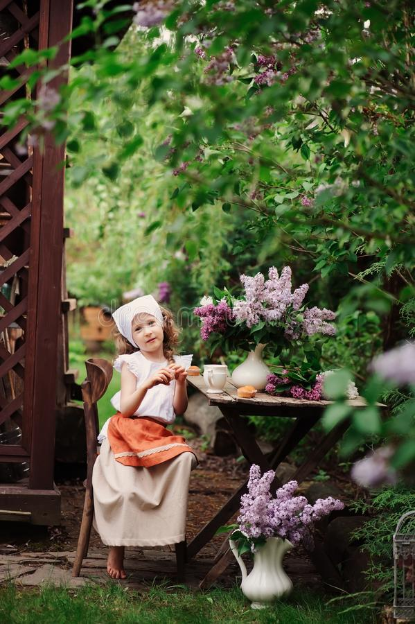 Kid girl at garden tea party in spring day with bouquet of lilacs syringa. Rustic wooden table and vintage dress royalty free stock photos