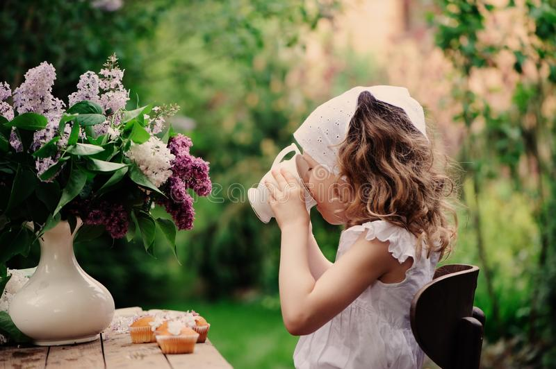 Kid girl at garden tea party in spring day with bouquet of lilacs syringa. Rustic wooden table and vintage dress stock photos