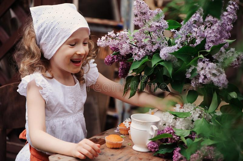 Kid girl at garden tea party in spring day with bouquet of lilacs syringa. Rustic wooden table and vintage dress royalty free stock image