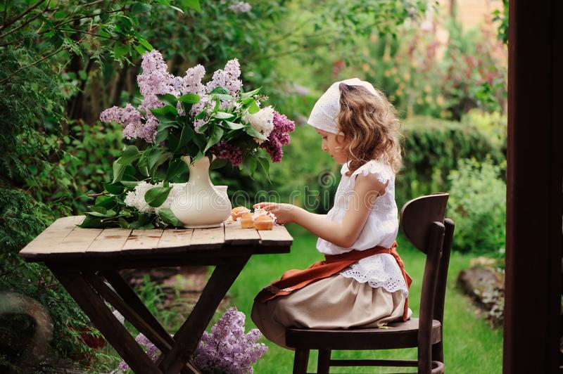 Kid girl at garden tea party in spring day with bouquet of lilacs syringa. Rustic wooden table and vintage dress stock images