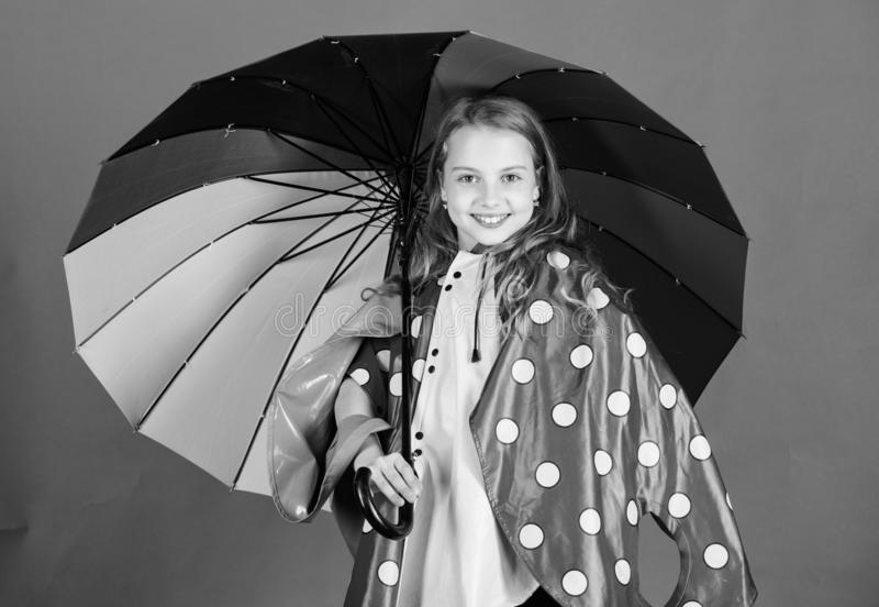 Kid girl happy hold colorful umbrella wear waterproof cloak. Enjoy rainy weather with proper garments. Waterproof stock image