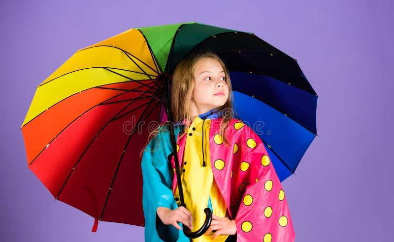 Kid girl happy hold colorful umbrella wear waterproof cloak. Waterproof accessories for children. Enjoy rainy weather. With proper garments. Waterproof stock photo