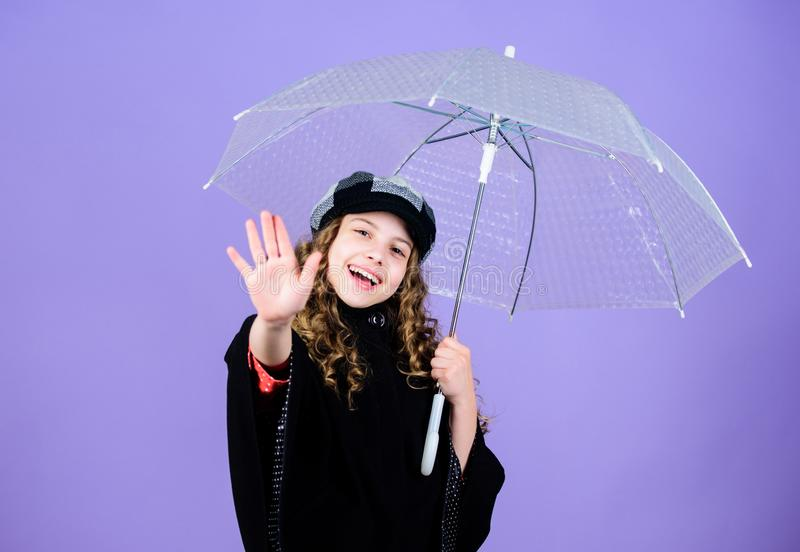 Kid girl happy hold transparent umbrella. Enjoy rainy weather with proper garments. Waterproof accessories make rainy stock images